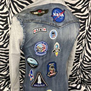 Acht Raumfahrten und zwei militärische Aufnäher auf einer blauen Jeansbluse mit grauen Ärmeln