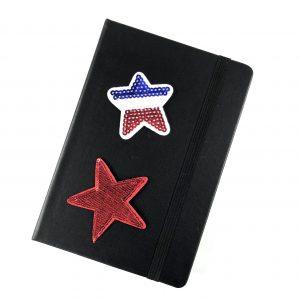 Roter Paillettenstern zusammen mit einem roten Paillettenstern-Bügelbild auf der Vorderseite eines schwarzen Tagebuchs