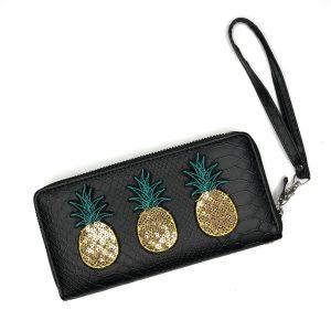 Drei goldfarbene Paillette-Ananas-Bügelbilder mit grünen Fruchtblättern auf einer schwarzen Lederbrieftasche