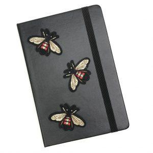 Drei Bienen mit rotem Mieder und hellen Flügeln bügeln Flecken auf einer schwarzen Tagesordnung