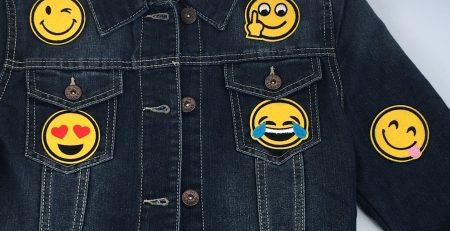 Fünf gelbe runde Emoji-Bügelflecken auf einer dunkelblauen Jeansjacke