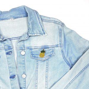 Kleines Ananas-Eisen auf Patch auf der Klappe einer Brusttasche einer leichten Jeansjacke